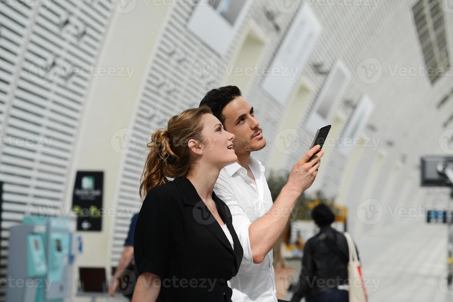 Les jeunes voyageurs d'affaires homme femme station publique à la recherche d'horaire photo