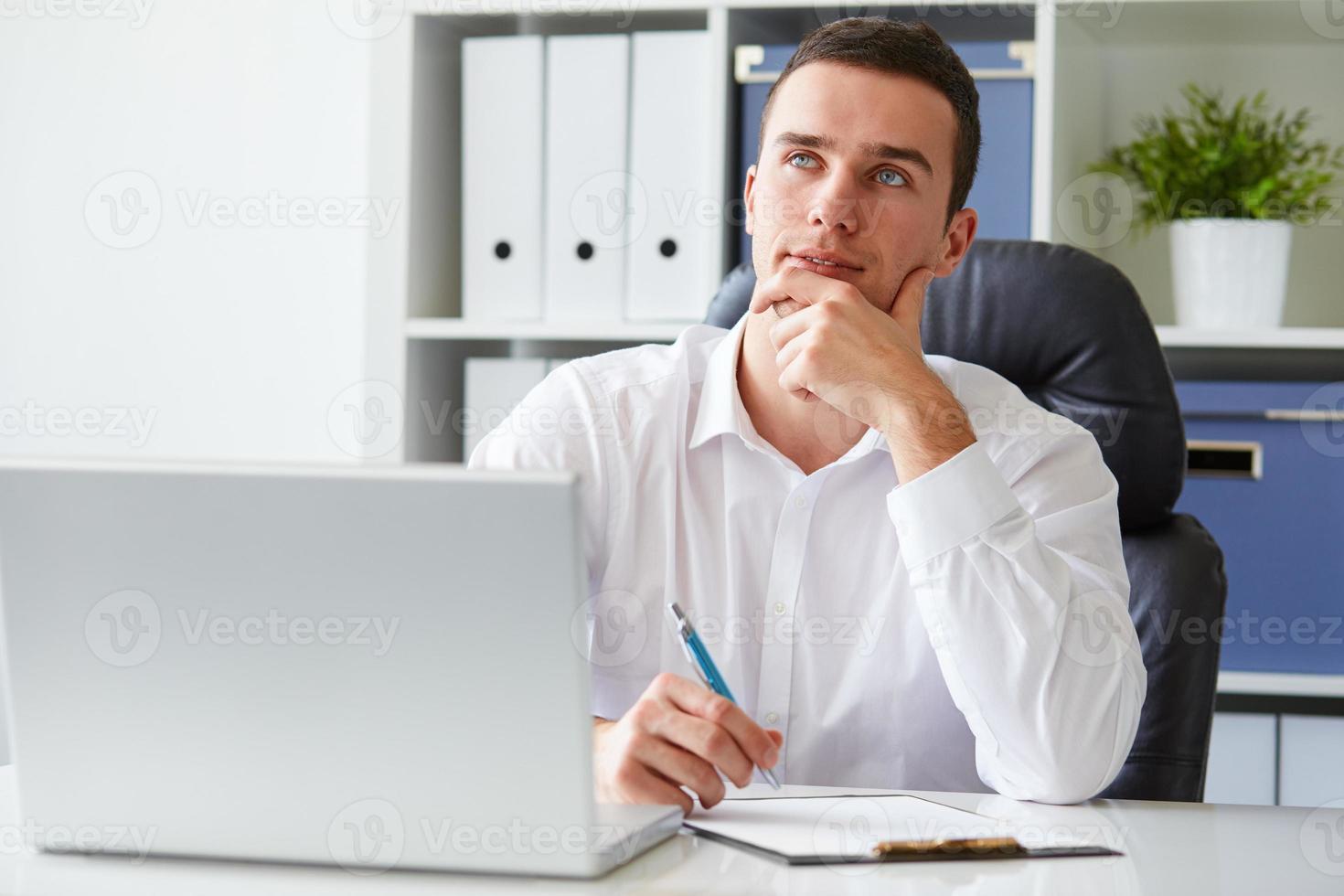 songeur jeune homme d'affaires avec ordinateur portable photo