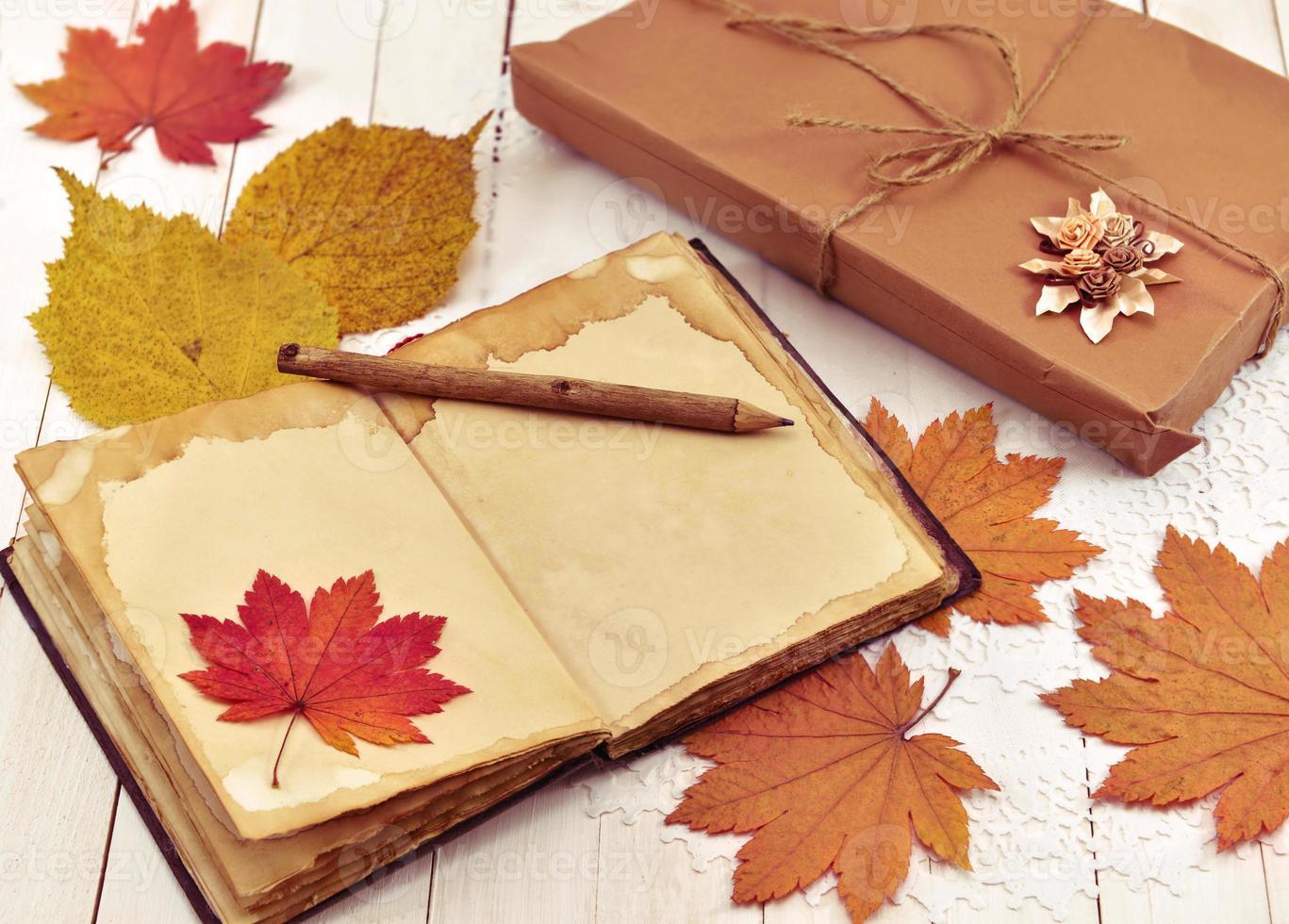 automne nature morte avec livre, feuilles et cadeau emballé photo