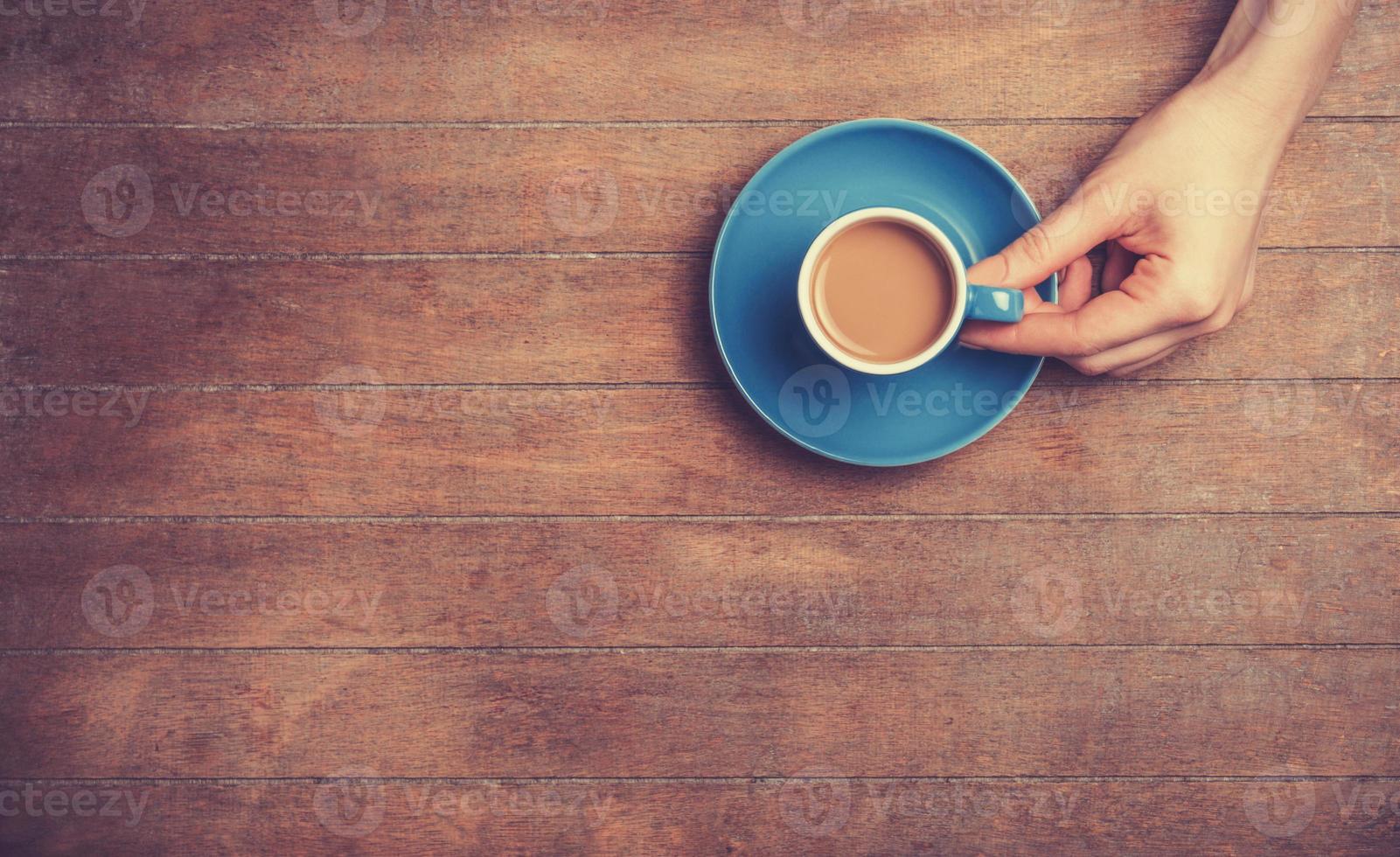 mains féminines tenant une tasse de café. photo