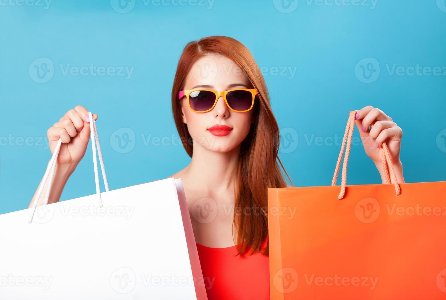 femmes rousse de style tenant des sacs à provisions sur fond bleu. photo