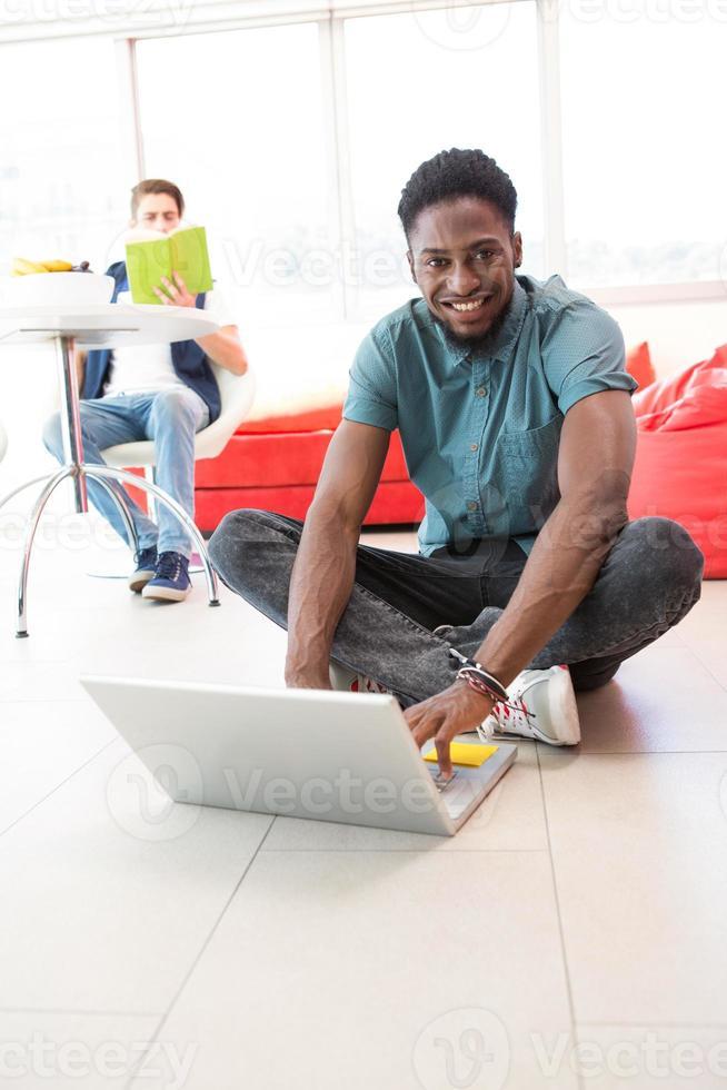 sourire, jeune homme, portable utilisation, sur, plancher photo