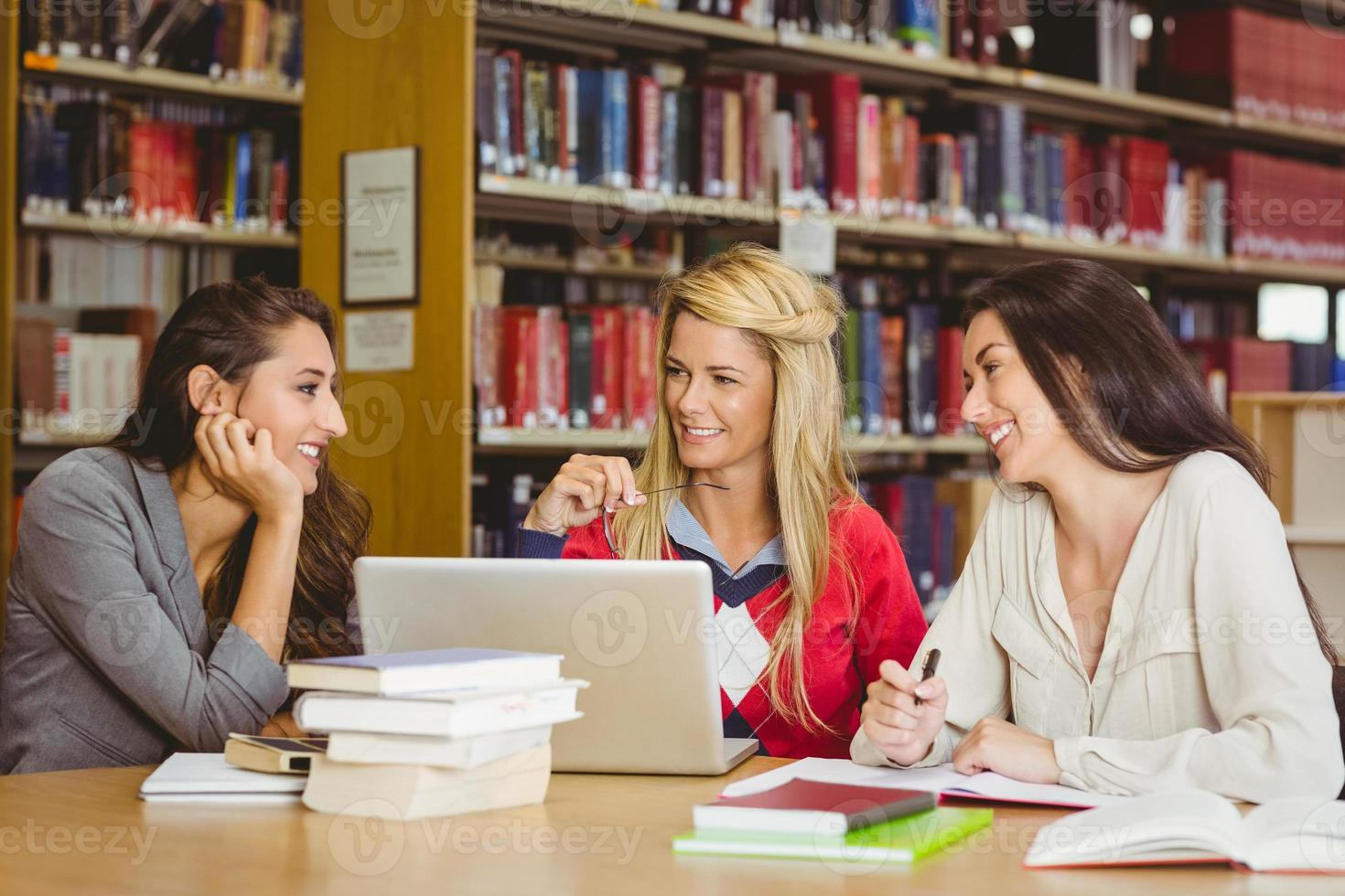 étudiant adulte souriant avec ses camarades de classe à l'aide d'un ordinateur portable photo