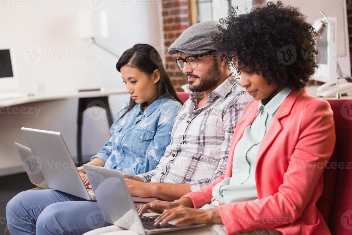 collègues occasionnels utilisant des ordinateurs portables sur le canapé photo
