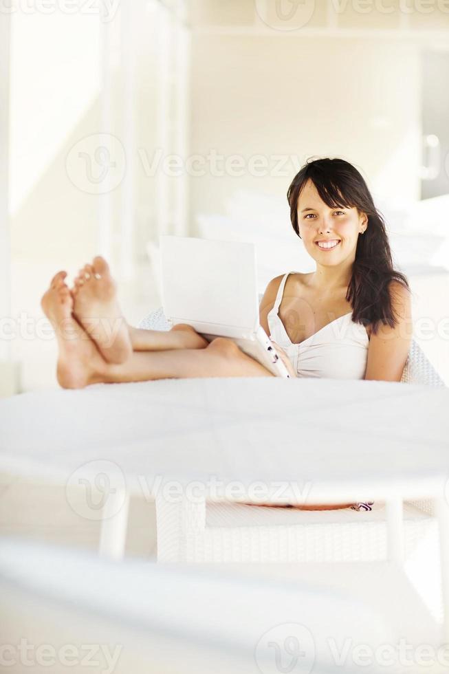 femme assise dans un fauteuil avec un ordinateur portable photo