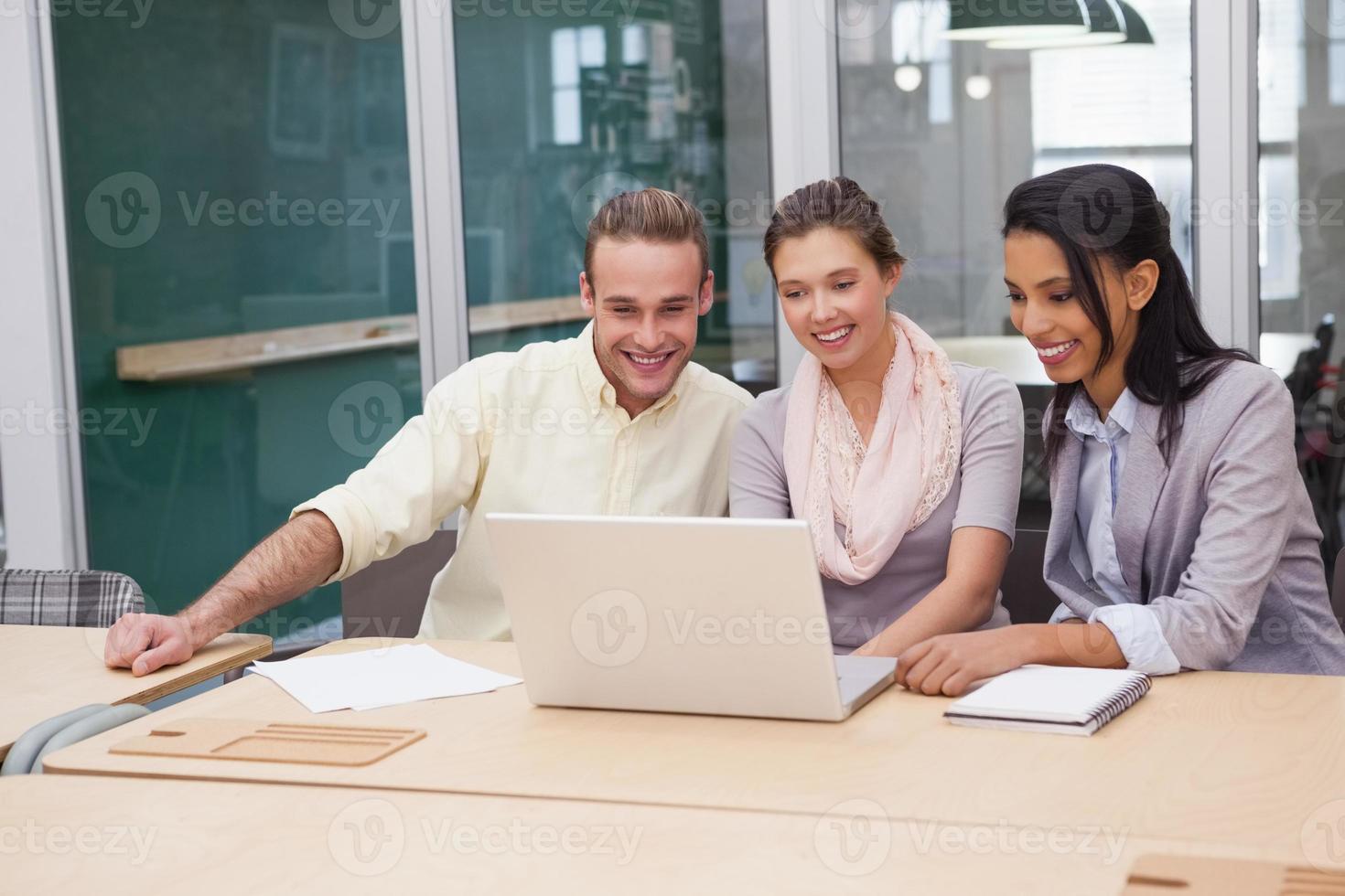 trois hommes d'affaires heureux travaillant ensemble sur un ordinateur portable photo