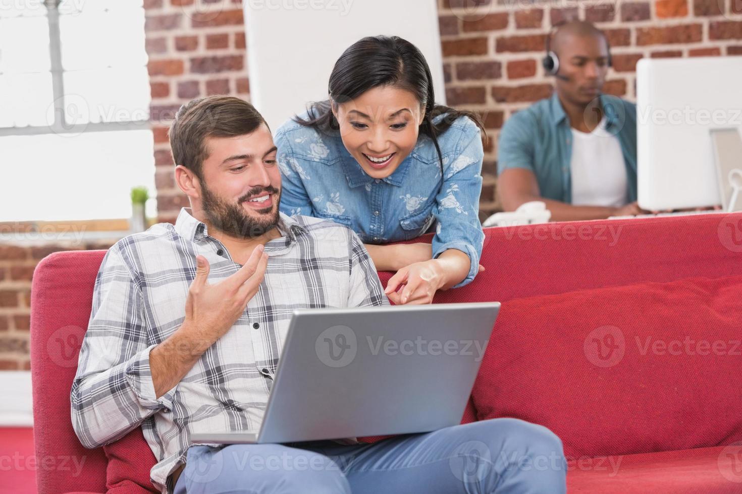 collègues occasionnels utilisant un ordinateur portable sur le canapé photo