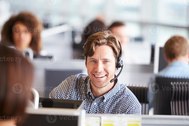 jeune homme travaillant dans le centre d'appels, à la recherche d'appareil photo