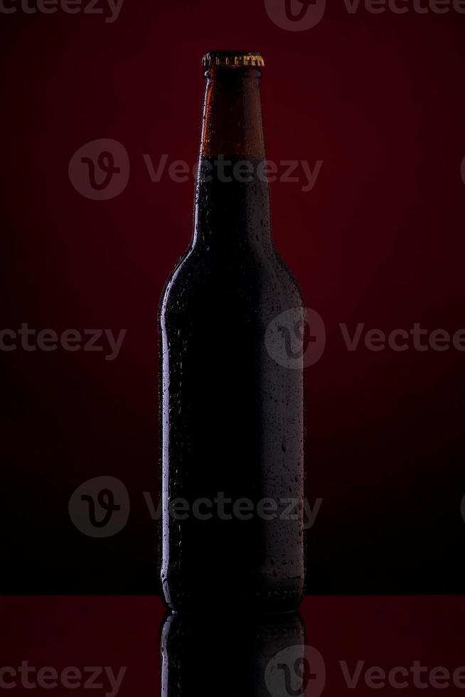 bouteille de bière avec des gouttes sur fond rouge foncé. photo