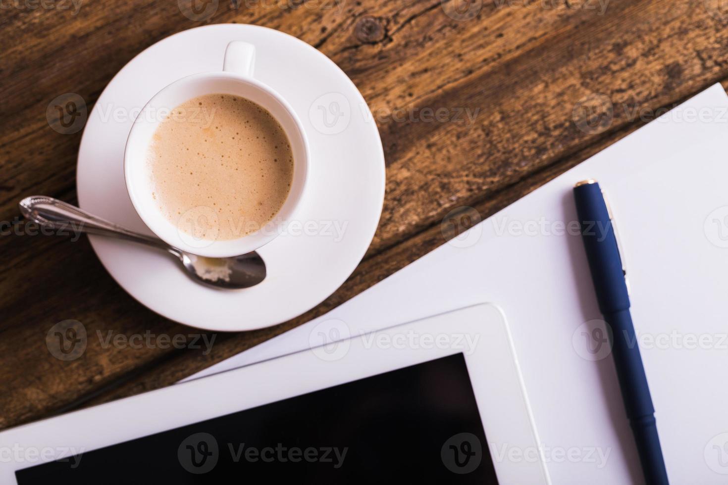 Tablette numérique et café sur fond de bois ancien photo