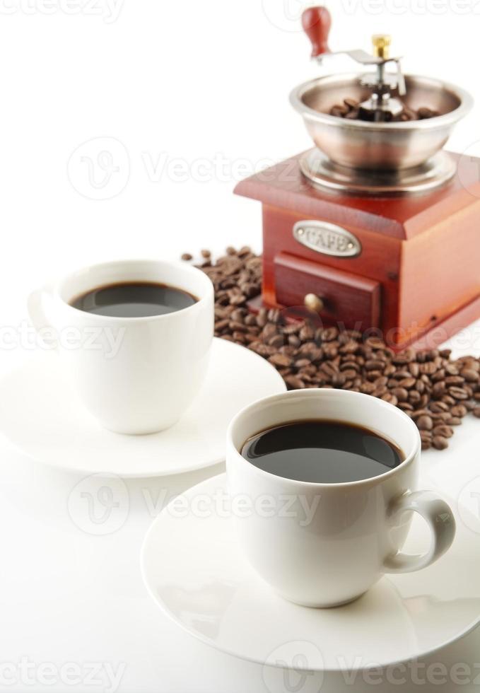 tasses de café avec soucoupe et moulin sur blanc photo
