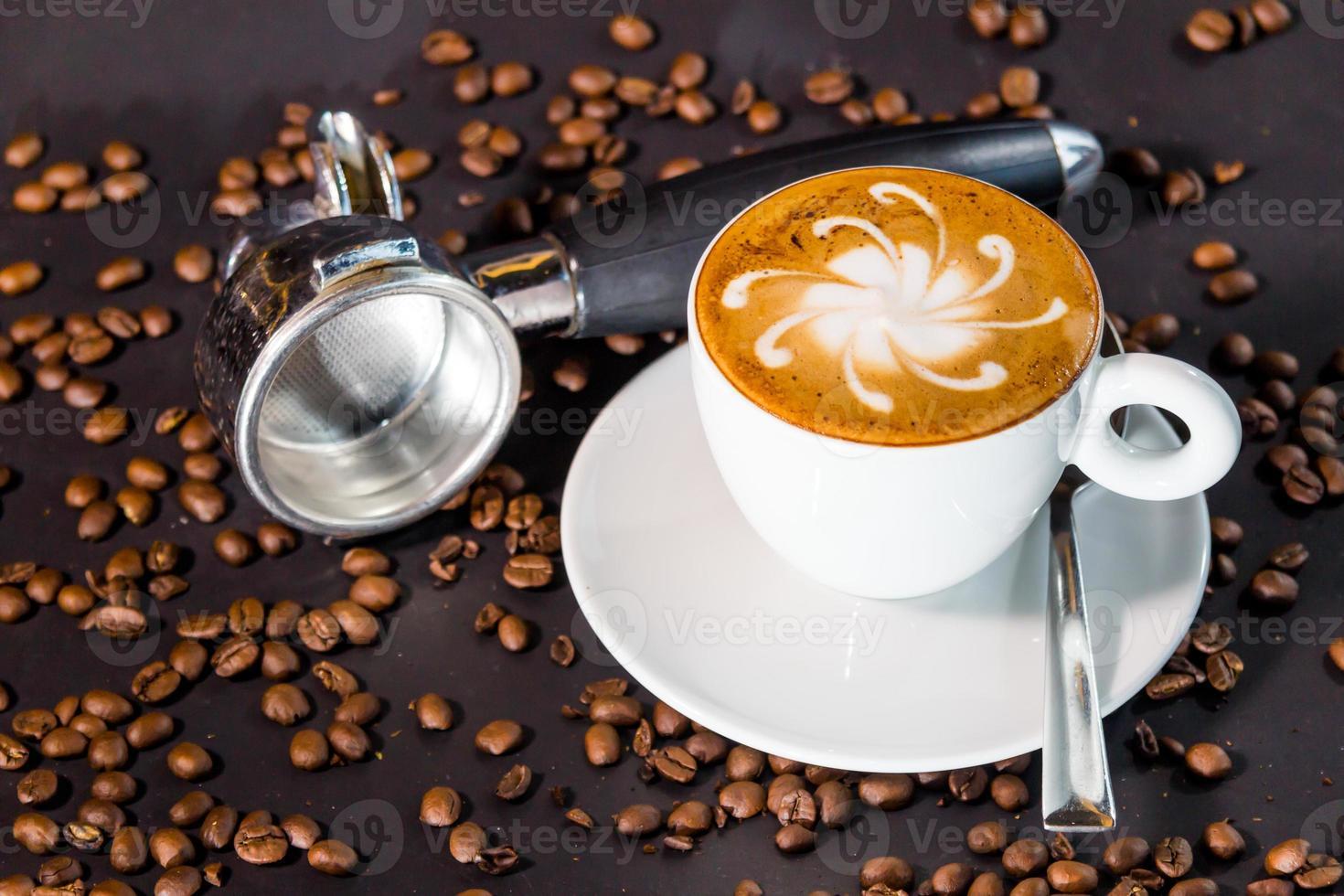 Tasse de café tardif et grains sur fond noir. photo
