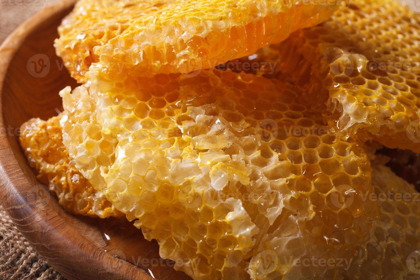 nid d'abeille doré frais sur macro de plaque de bois. horizontal photo