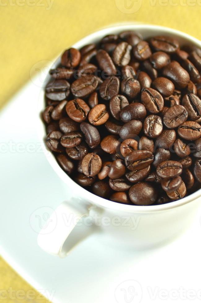 tasse à café blanche pleine de grains de café photo