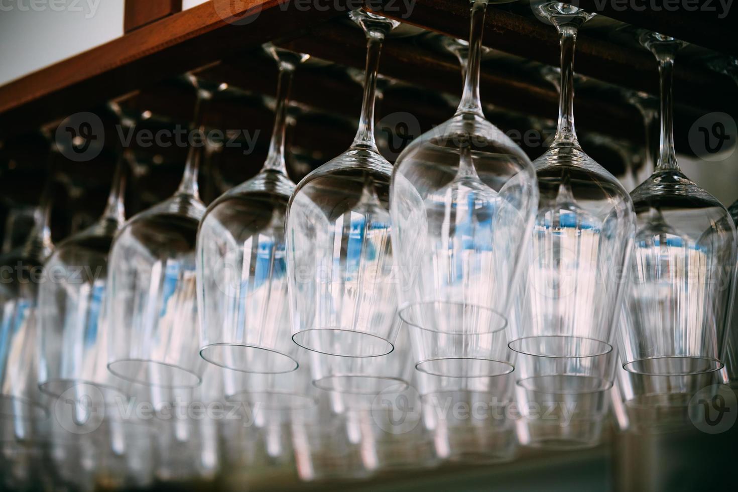 verres vides pour le vin au-dessus du support de bar. verres à vin suspendus photo