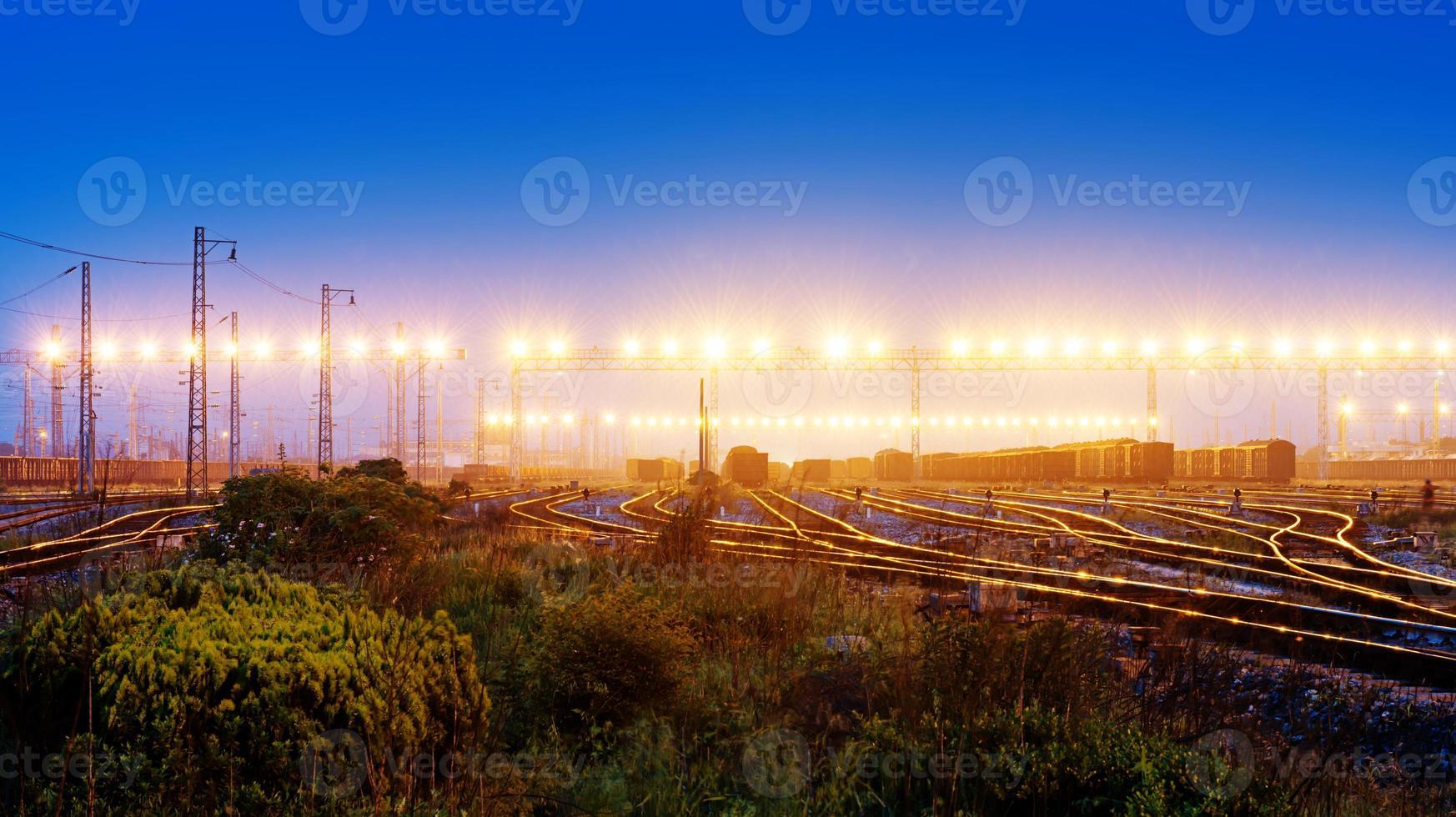 Plate-forme de train de marchandises au coucher du soleil avec conteneur photo
