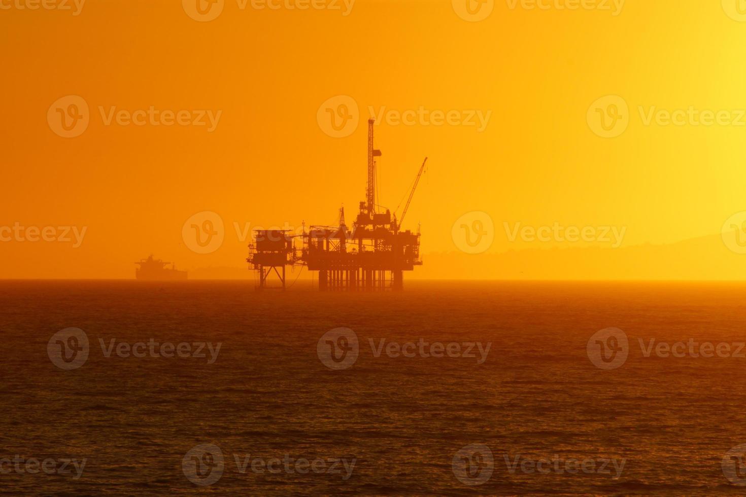plate-forme pétrolière de plage au coucher du soleil photo