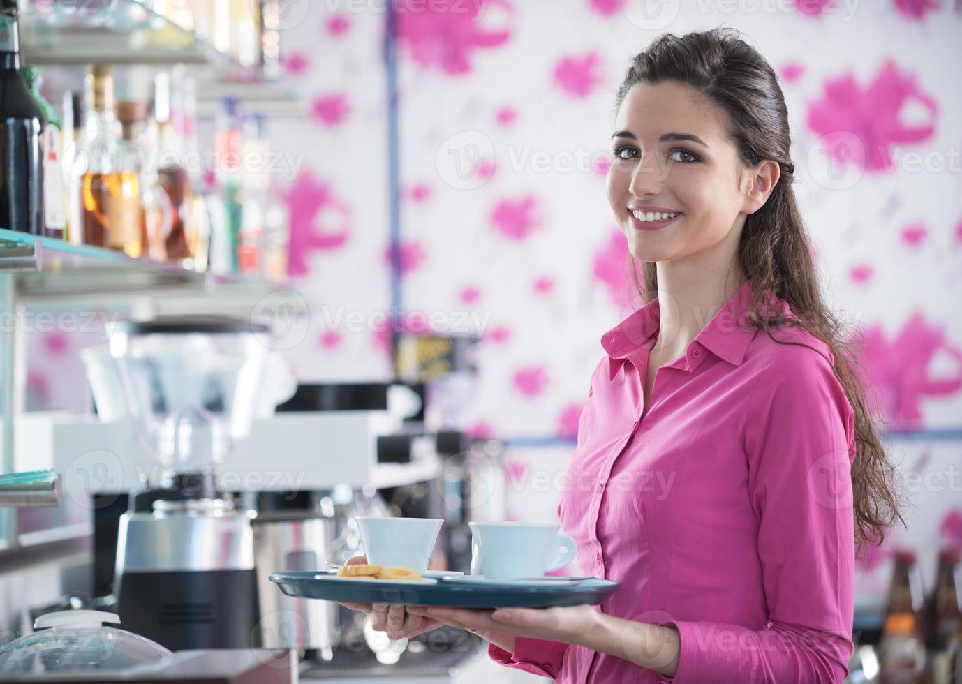 jeune serveuse souriante servant du café au bar photo