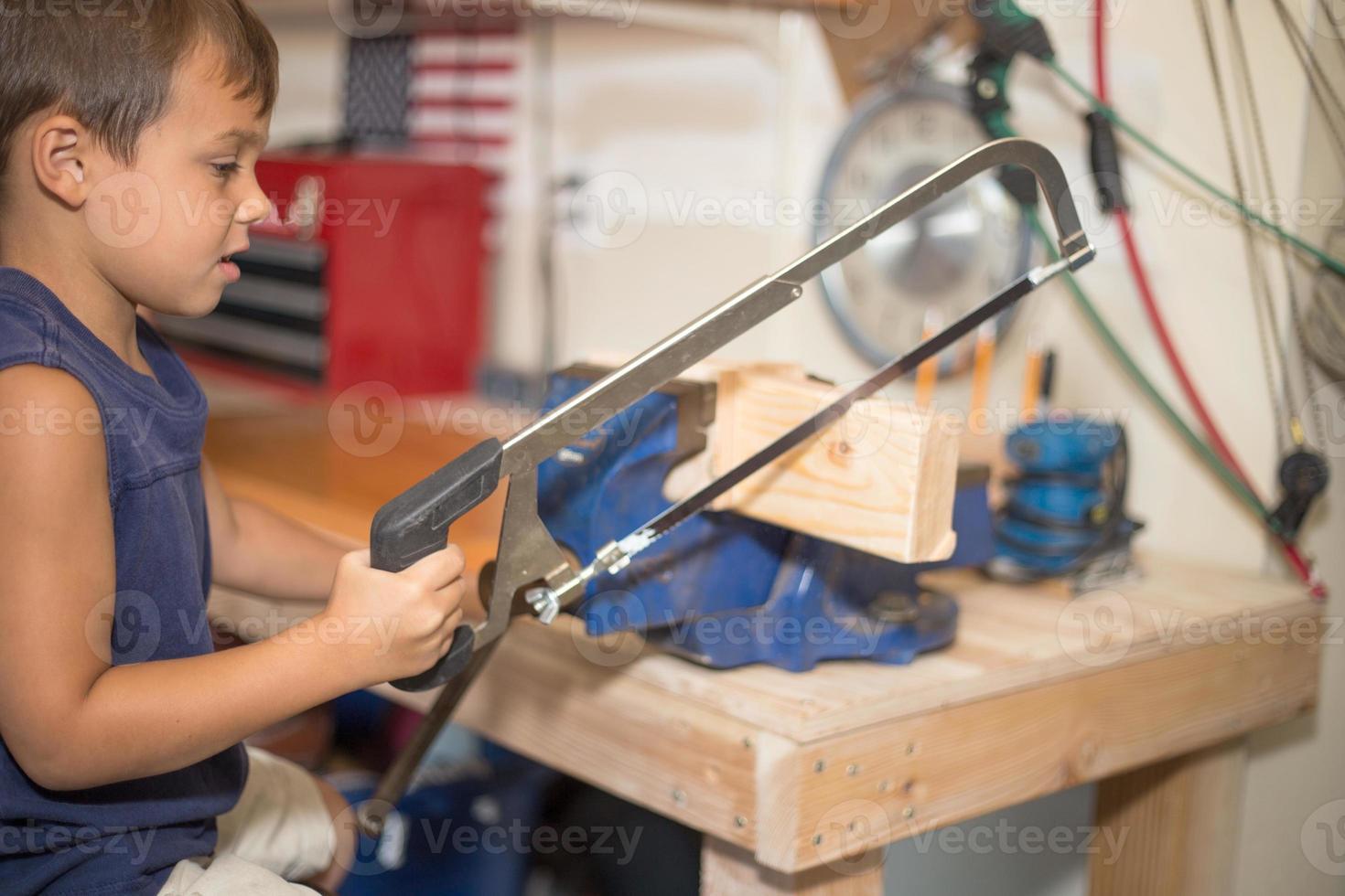 garçon utilisant une scie. photo