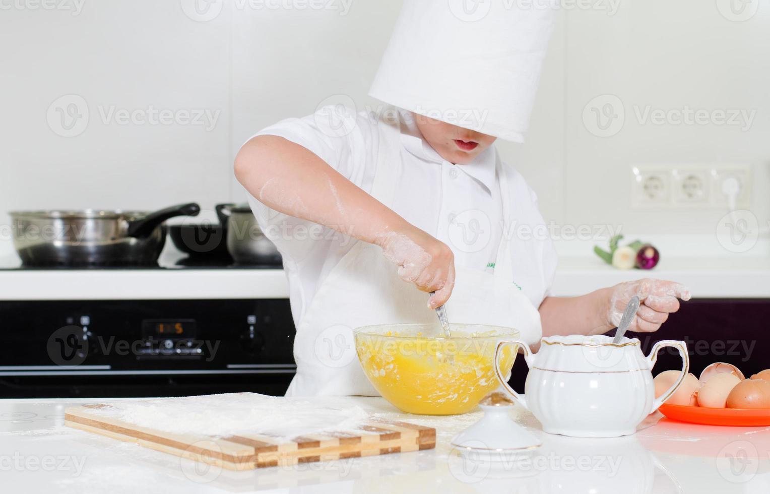 mignon petit garçon dans une grande toque debout cuisson photo