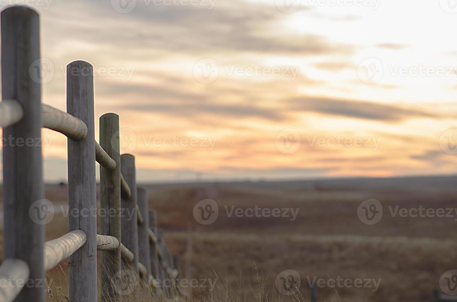 clôture menant le regard vers un coucher de soleil en espace ouvert photo