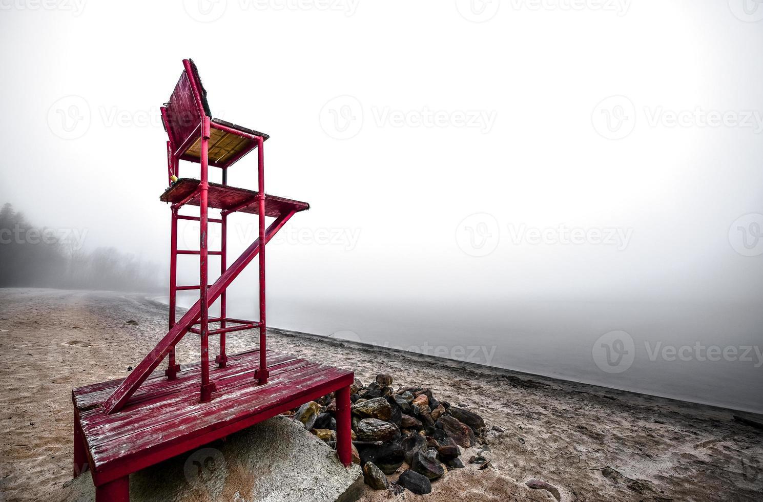 chaise de sauveteur vide sur une plage brumeuse. photo