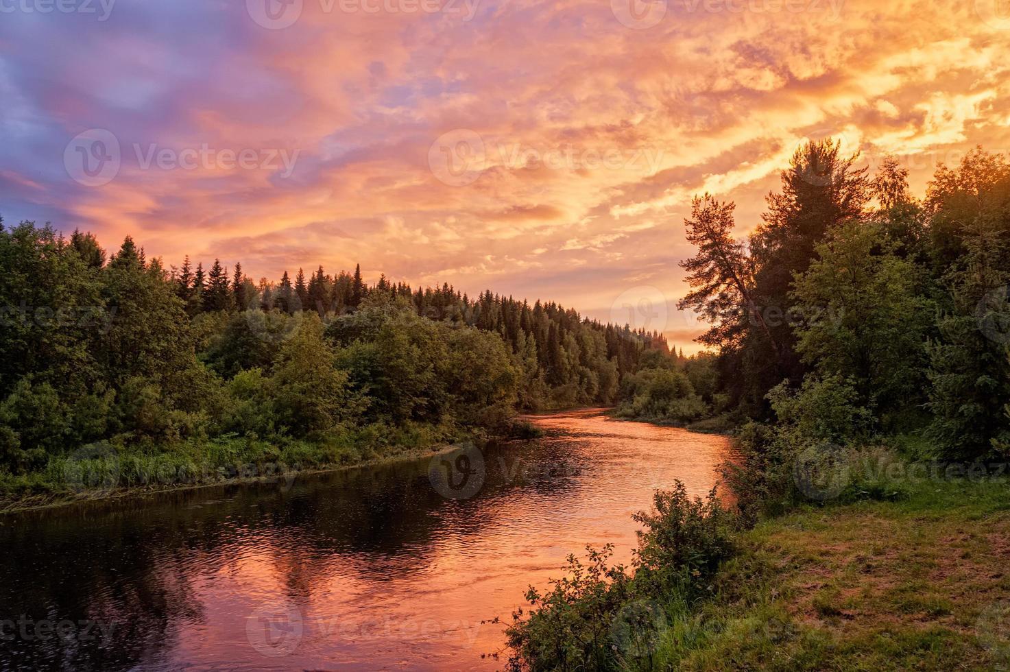 coucher de soleil spectaculaire lumineux sur la rivière avec forêt le long de la rivière photo