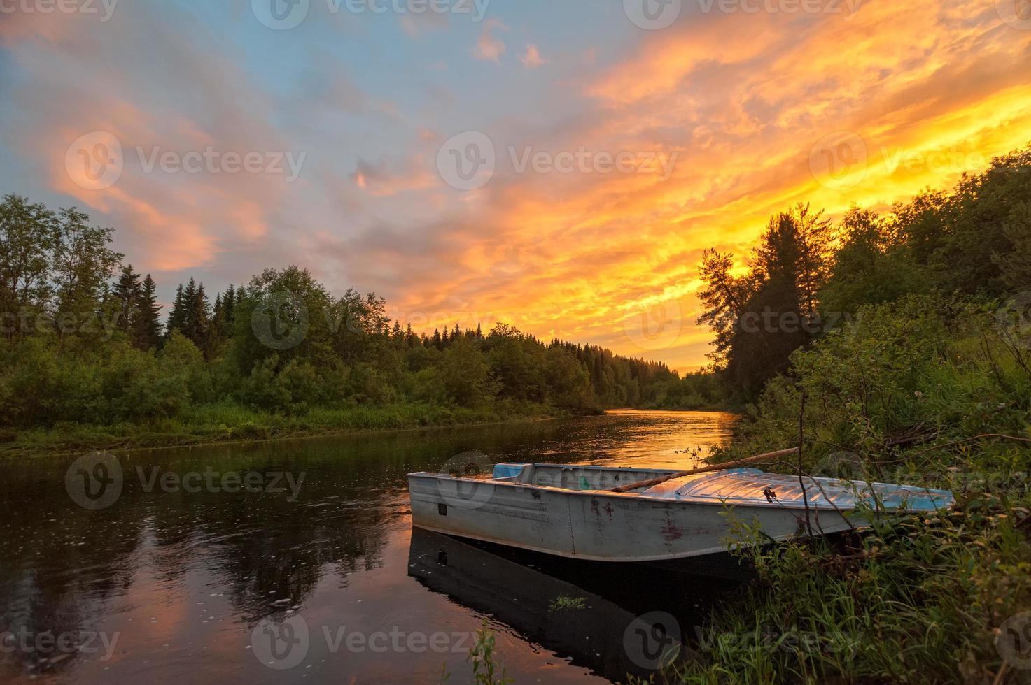 coucher de soleil spectaculaire lumineux sur la rivière avec bateau en premier plan photo