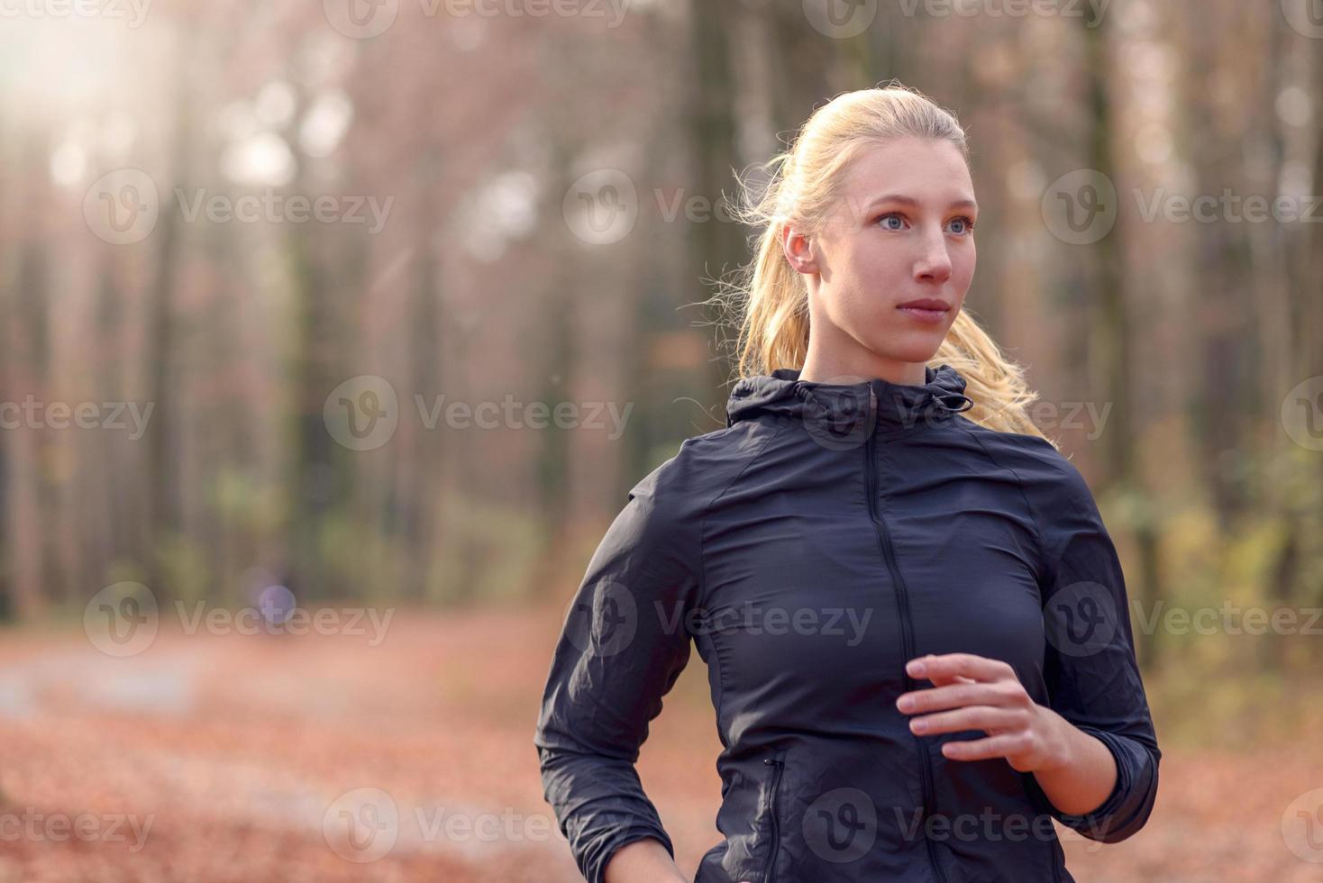 Jolie jeune femme en forme de jogging dans les bois photo