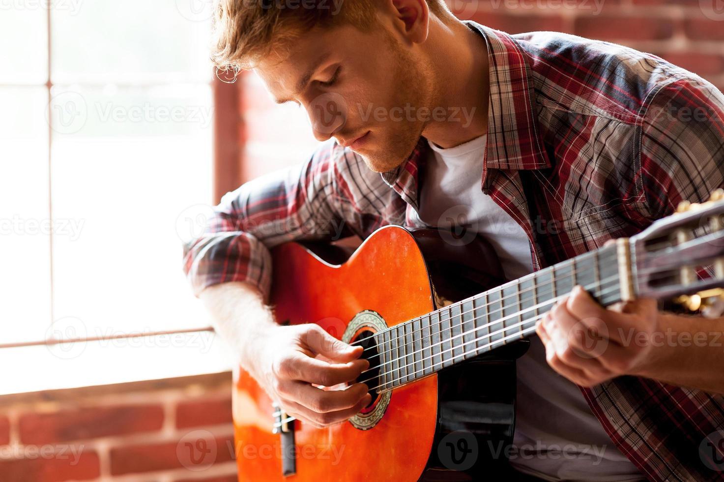 bel homme jouant de la guitare. photo