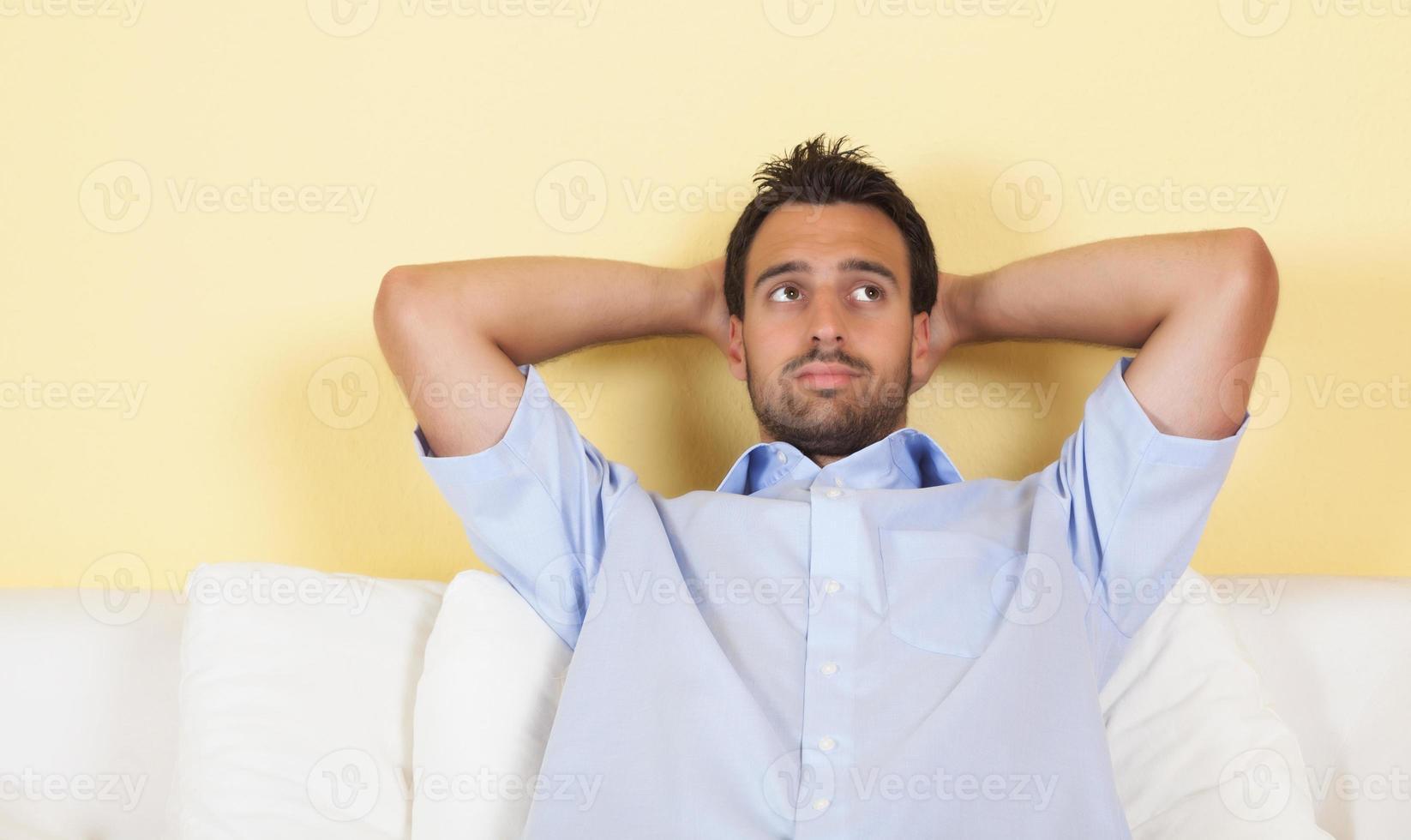 homme latin réfléchi sur un canapé photo