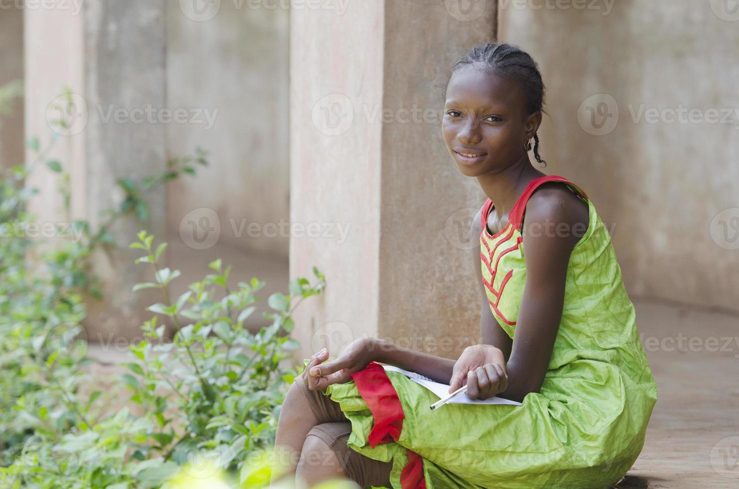 magnifique écolière assise sur les escaliers (symbole de l'éducation) photo