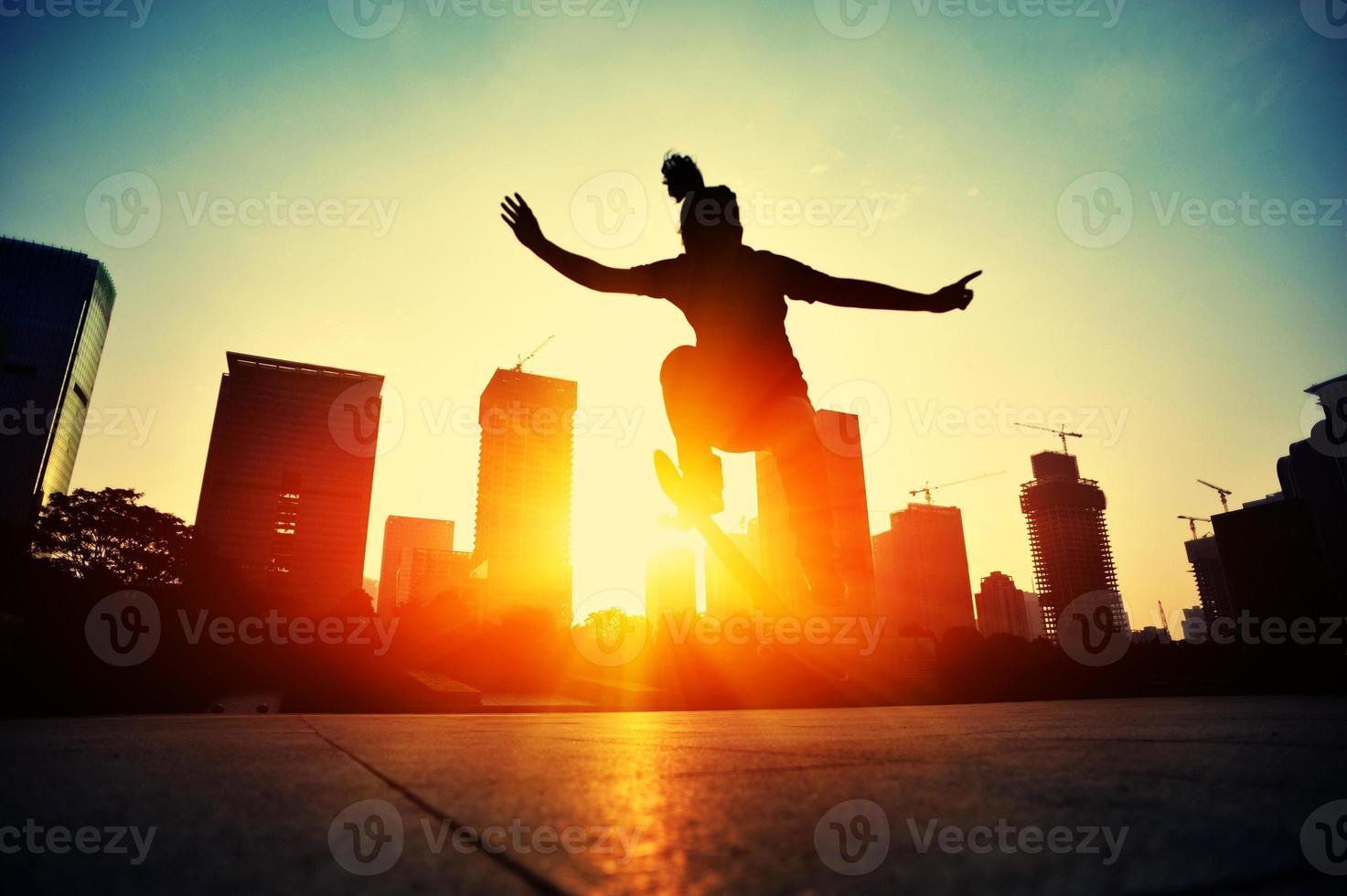 planche à roulettes femme sautant au lever du soleil photo