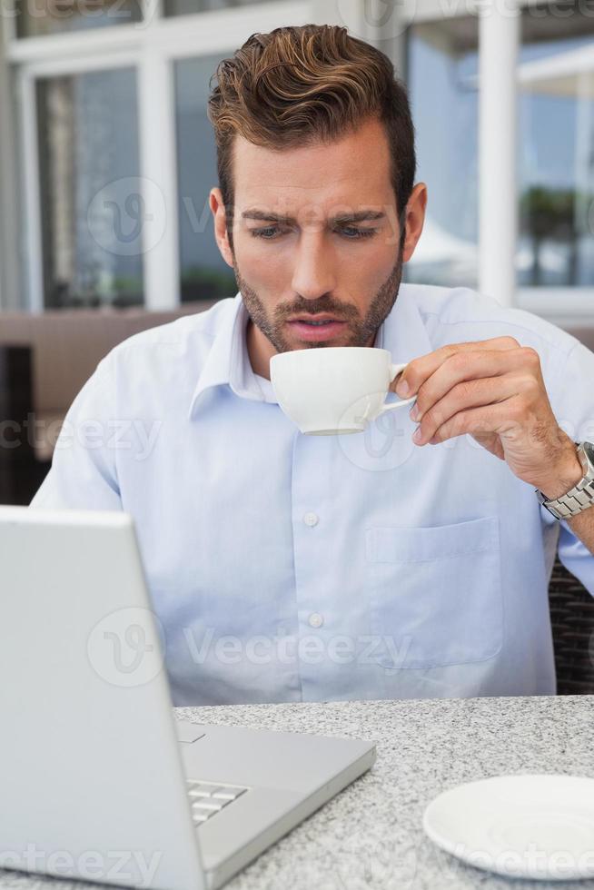 bel homme d'affaires travaillant avec un ordinateur portable, boire du café photo