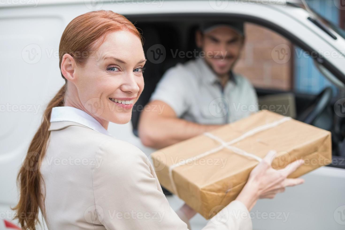 chauffeur-livreur remettant le colis au client dans sa camionnette photo