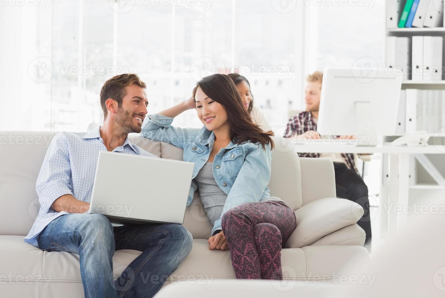 designers souriants travaillant ensemble sur ordinateur portable sur le canapé photo