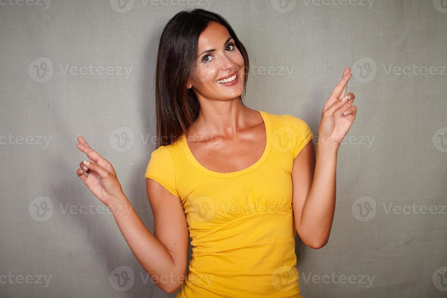 femelle charismatique croisant les doigts tout en souhaitant photo