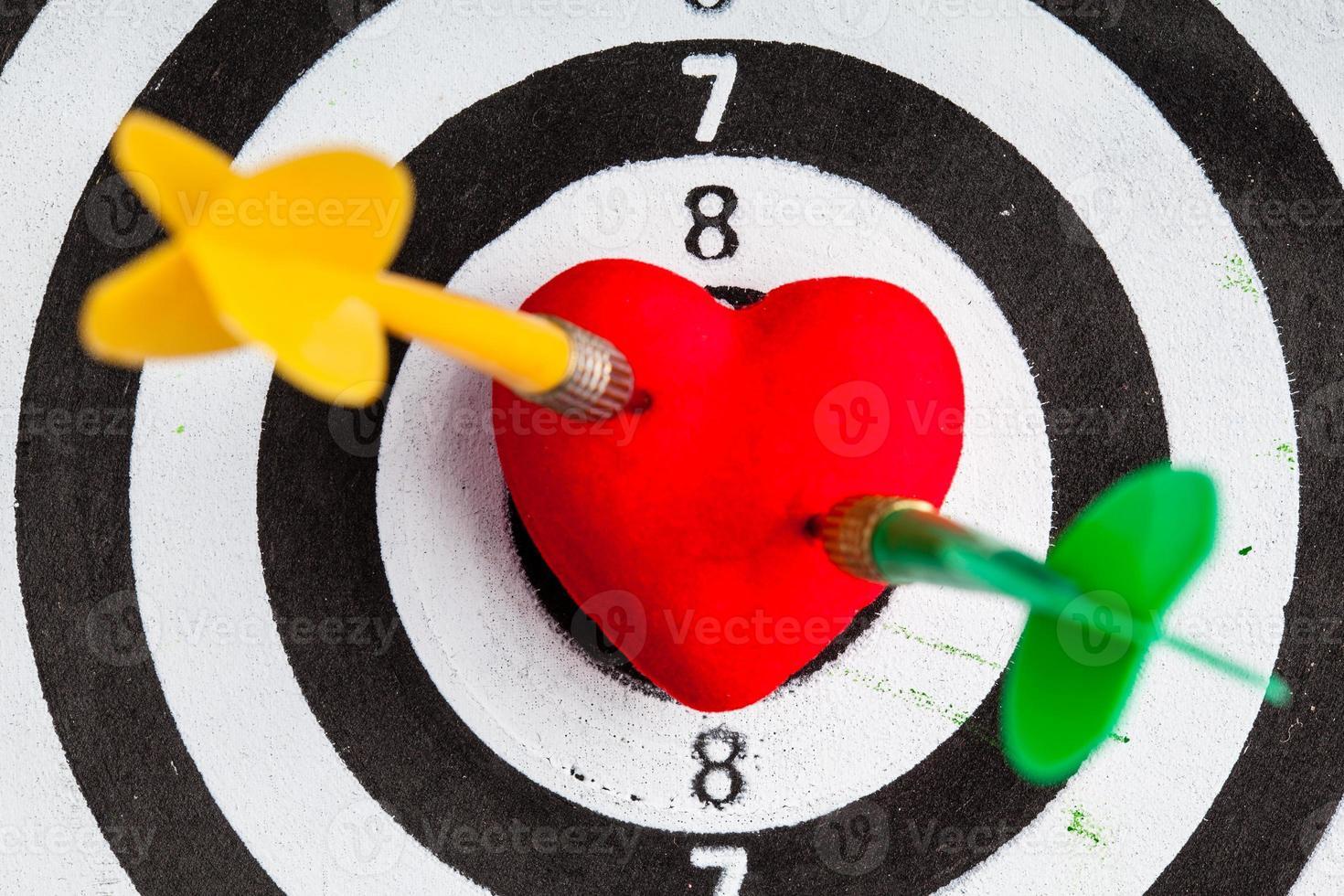 cible noir blanc avec des fléchettes dans l'amour de coeur comme bullseye photo