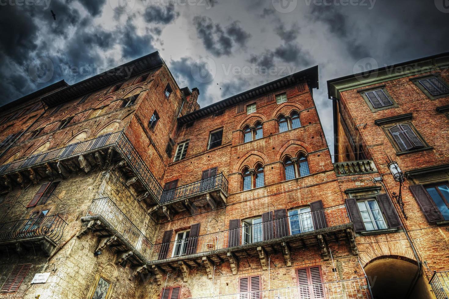 vieux bâtiment à sienne sous un ciel dramatique photo