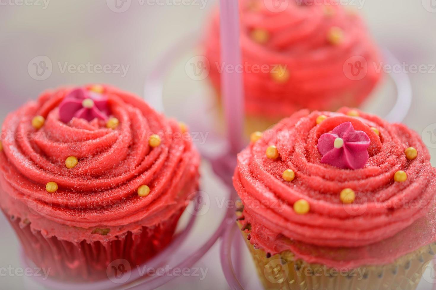 Trois petits gâteaux bollywood rose kitsch sur un stand de gâteau photo