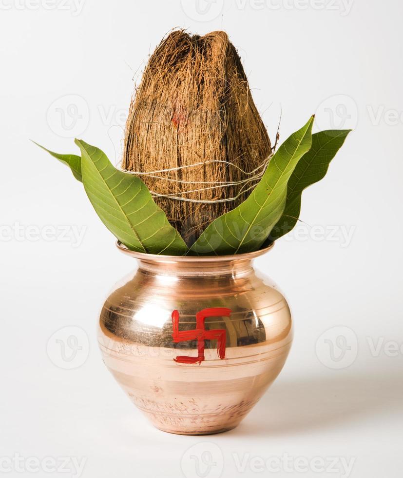 kalash / pot en cuivre et noix de coco et feuille de mangue photo