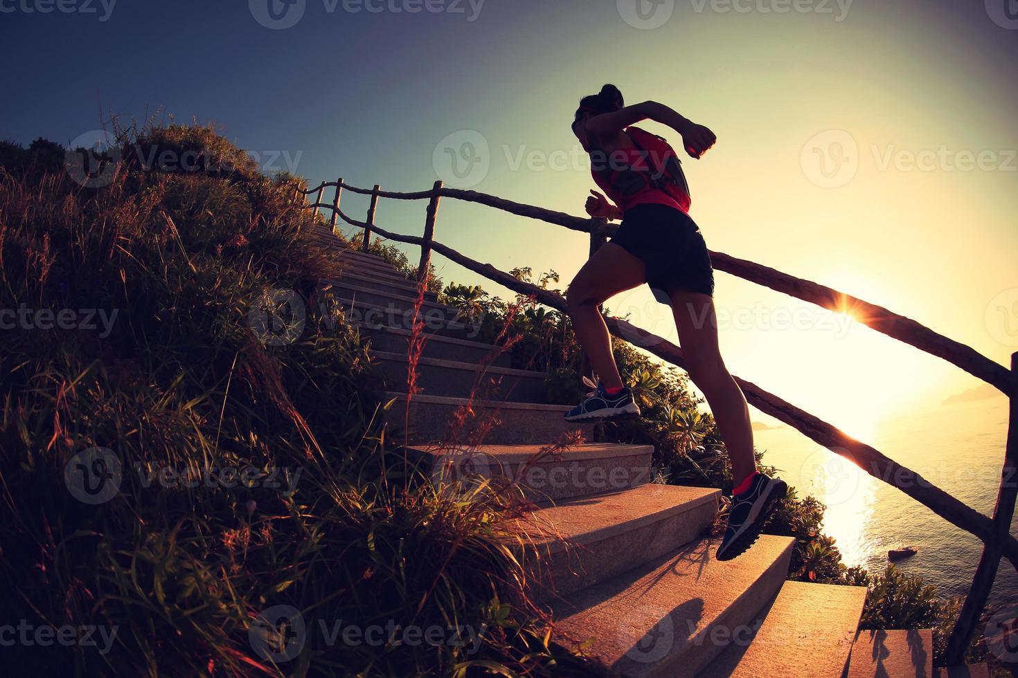 Fitness femme coureur trail courir sur les escaliers de montagne en bord de mer, photo