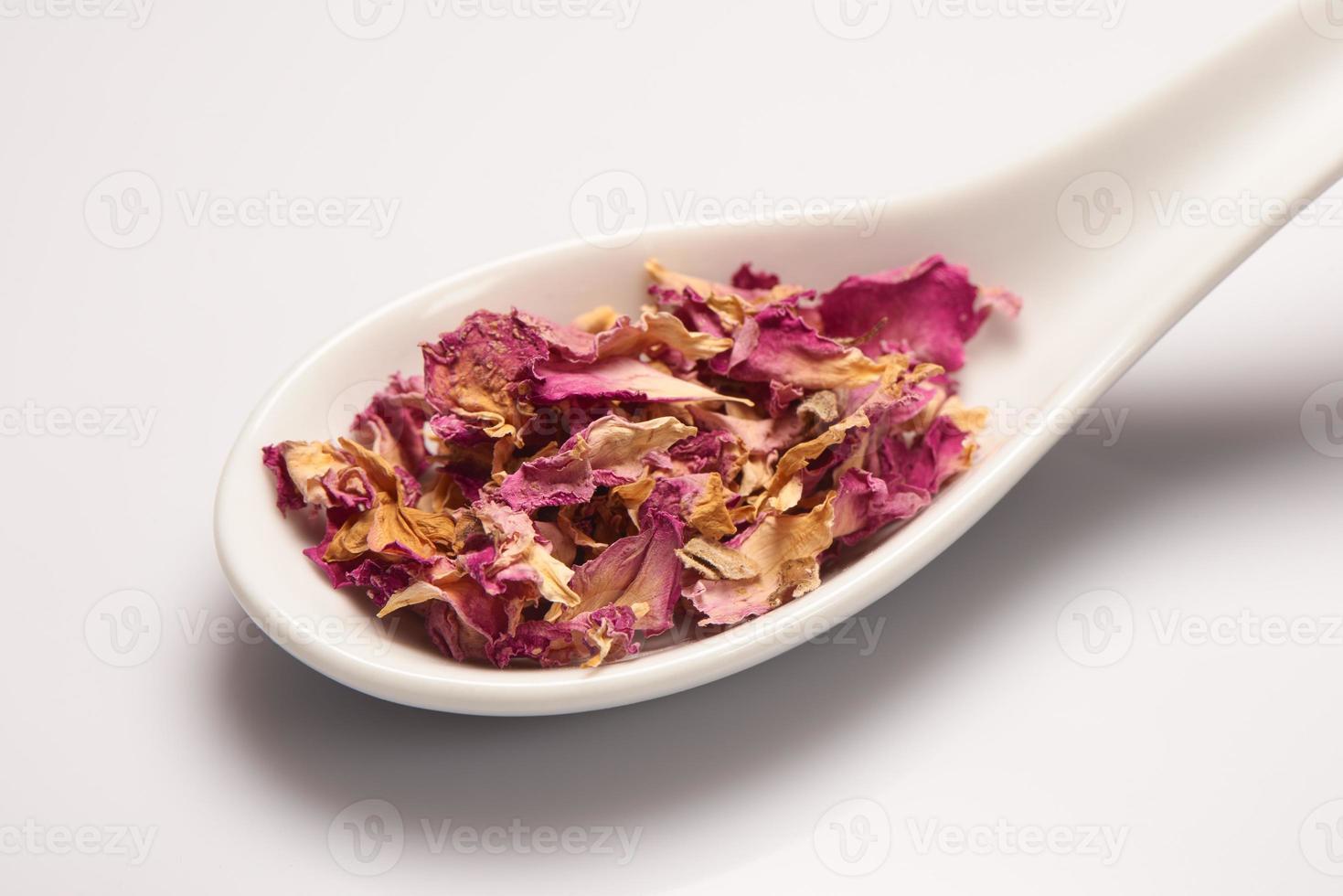 tas de feuilles de rose sec dans une cuillère en céramique blanche photo