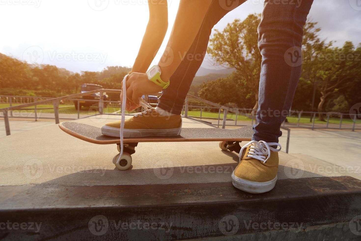Skateboader mains attachant lacet sur planche à roulettes photo