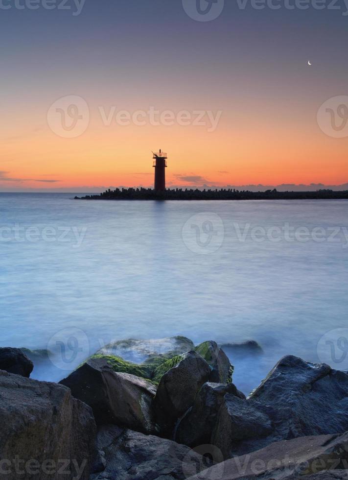 paysage marin au coucher du soleil - phare sur la côte photo