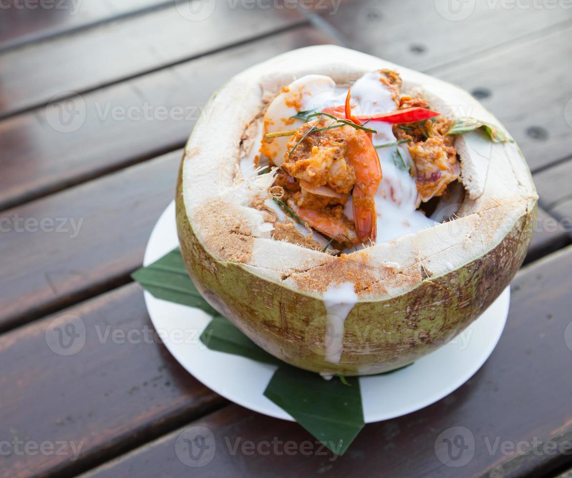fruits de mer à la vapeur de curry dans une tasse de noix de coco photo