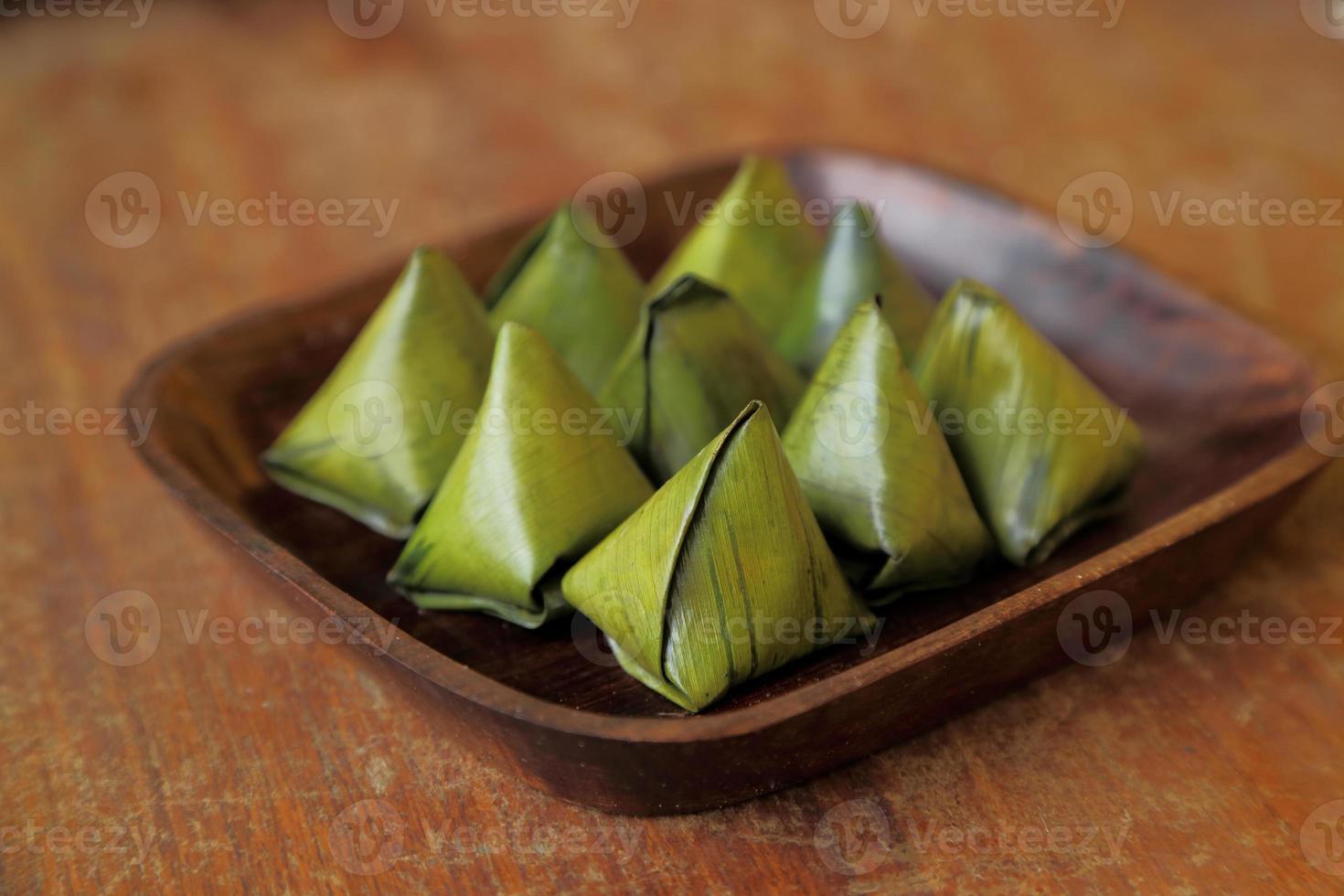 dessert thaïlandais enveloppé dans des feuilles de bananier sur un plat en bois. photo