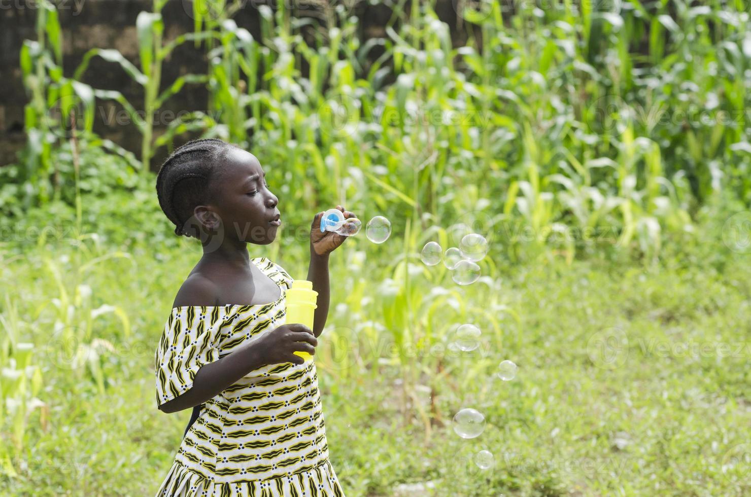 Fille africaine jouant avec des bulles de savon à l'extérieur à Bamako, Mali photo