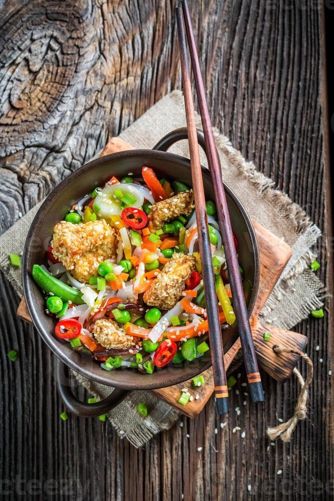 Gros plan du chinois mélanger les légumes avec du poulet au sésame photo