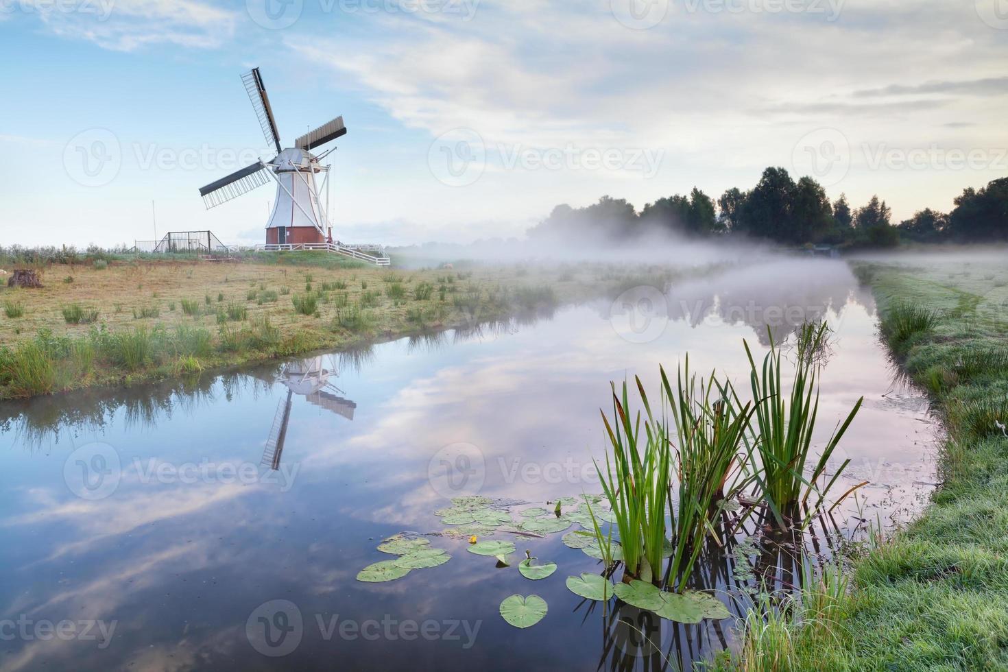 Moulin à vent hollandais blanc dans le matin brumeux photo